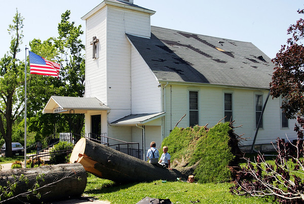The Joplin Globe/T. Rob Brown<br /> Two small children are dwarfed by a large, uprooted tree next to the Newtonia (Mo.) Baptist Church Monday afternoon, May 12, 2008. The church is a location for storm relief and cleanup support.