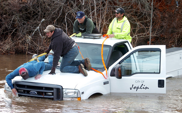 Globe/T. Rob Brown<br /> City of Joplin Public Works Department employees work to remove a city pickup truck from the waters of Turkey Creek near Main Street Wednesday afternoon, Feb. 11, 2009. The city recently replaced a sewer line in that location.