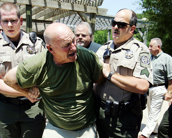 Globe/T. Rob Brown<br /> Newton County Sheriff's Department deputies arrest Cecil Scribner, an employee of the Swimmin' Hole, Friday afternoon, June 26, 2009, at the water park.