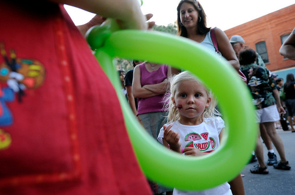 Liana Jacobson, of The Balloon Gal Co. in Ft. Collins, left, makes a balloon hat for Emmy Tecu, 3, of Longmont, while her mother Tara Tecu, right, smiles with joy at the 2010 Festival on Main on Friday, Aug. 27, in Longmont.<br /> Jeremy Papasso/ Camera