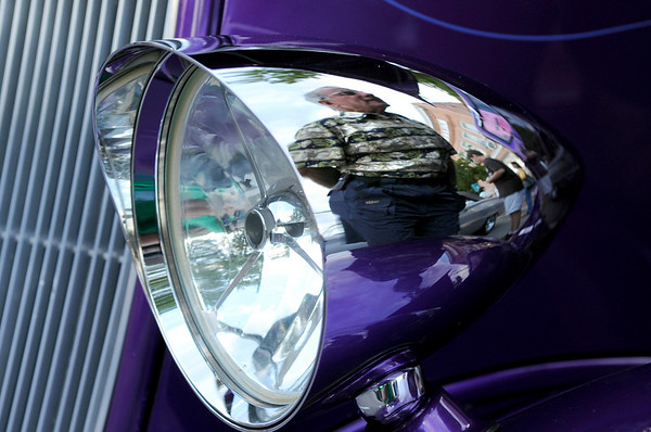 Gary Rubin, of Longmont, is reflected in the headlight of a 1933 Ford Coupe at the 2010 Festival on Main on Friday, Aug. 27, in Longmont. The car was part of the car show and Rubin was seeing what kind of motor the vehicle had under the hood.<br /> Jeremy Papasso/ Camera