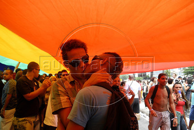 A couple kisses under a big rainbow flag during the 16th. Gay Pride Parade in Copacabana beach, Rio de Janeiro, Brazil, October 9, 2011. (Austral Foto/Renzo Gostoli)