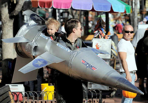 Andrew Matranga (right0 and his son Lochlan Matranga (left), 19 months, fly a sortie down the mall during the Munchkin Masquerade on the Pearl Street Mall in Boulder, Colorado October 31, 2011.  CAMERA/Mark Leffingwell
