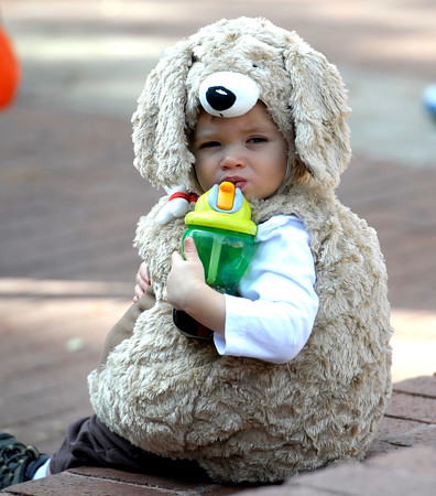 Kolton Rodemich, 17 months, takes a break to get a drink during the Munchkin Masquerade on the Pearl Street Mall in Boulder, Colorado October 31, 2011.  CAMERA/Mark Leffingwell