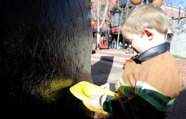 Nat Hatch, 4, washes out his firemen's helmut at the water feature during the Munchkin Masquerade on the Pearl Street Mall in Boulder, Colorado October 31, 2011.  CAMERA/Mark Leffingwell
