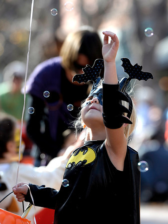 Samantha Sessa, 6, reaches for bubbles during the Munchkin Masquerade on the Pearl Street Mall in Boulder, Colorado October 31, 2011.  CAMERA/Mark Leffingwell