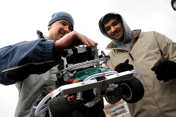 """Jeff Boody, of Boulder, left, and Nasser Grainawi, of Erie, work to mount an Iphone on the top of their vehicle during the 2011 SparkFun Autonomous Vehicle Competition on Saturday, April 23, in Boulder. Boody and Grainawi were competing as Team """"Planet Express."""" The competition is a race around the SparkFun building using vehicles, both on the ground and in the air, that navigate themselves with a GPS device and/or sensors. For more photos and video go to  <a href=""""http://www.dailycamera.com"""">http://www.dailycamera.com</a><br /> Jeremy Papasso/ Camera"""
