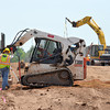 Two workers remove dirt and smooth out an area as contruction of a sound wall continues on Interstate 35 Wednesday afternoon.  The I-35 sound wall Project from Main Street to approximately 1200 feet north of Lindsey Street is a $1.4 million project managed by ODOT with Manhattan Road and Bridge Construction Company of Oklahoma City as their contractor.  This project is anticipated to be complete by early fall.<br /> Transcript Photo by Kyle Phillips