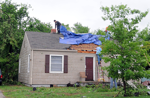 Workers cover a roof on Kansas St., Friday, April 13, 2012,  after a tornado tore off the roof. Photo by Jerry Laizure