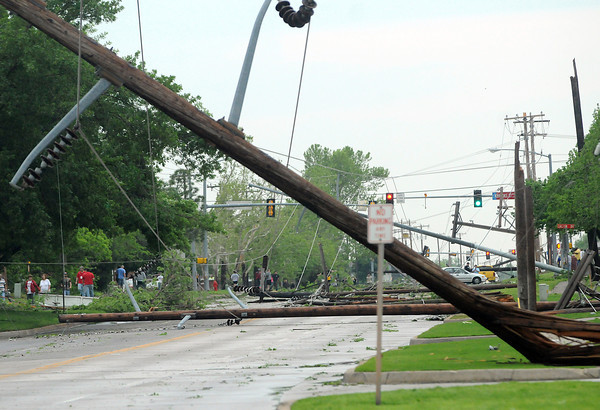 Reisdents and others in the neighborhood around Brook St. and 24th Ave. SW look at the utility poles and other damage Friday, April 13, 2012, caused by a tornado skipped through Norman. 24th Ave. NW was closed from State Highway 9 to Brooks St. Photo by Jerry Laizure