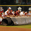Oklahoma grounds crew members and players roll out the tarp to cover the infield, Friday, April 13, 2012, prior to a rain storm and tornado that it Norman. Phoot by Jerry Laizure