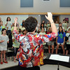 Sandy Knudson, director of the Norman Childens Chorus, rehearses the chorus as it prepares for it's 20th anniversary program. Photo by Jerry Laizure
