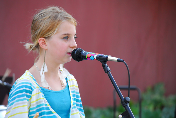 """Madison Evans, 11, sings with the band """"Grey Street"""" as they perform Friday evening at the Kids Corner during the 2nd Friday Art Circuit.<br /> Kyle Phillips/The Transcript"""