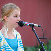 "Madison Evans, 11, sings with the band ""Grey Street"" as they perform Friday evening at the Kids Corner during the 2nd Friday Art Circuit.<br /> Kyle Phillips/The Transcript"