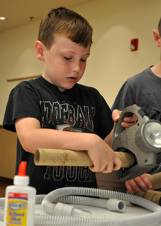 "Thomas Jones, 9, son of Linda Jones, comes up with an idea for his droid during Star Wars week at the Noble Public Library on Wednesday. The workshop encourages kids to create a ""droid"" with materials to win a prize. Workshop was taught by Mark Heisey. Julie Bragg/ The Transcript"
