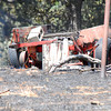 A trailer smolders after firefighters put out a fire  on 120th Ave. SE, just south of E. Etowah Rd. in Slaughterville, Friday afternoon.  About 20 acres burned before firefighters were able to get it under control.  There were no structures damaged in the blaze.<br /> Kyle Phillips/The Transcript