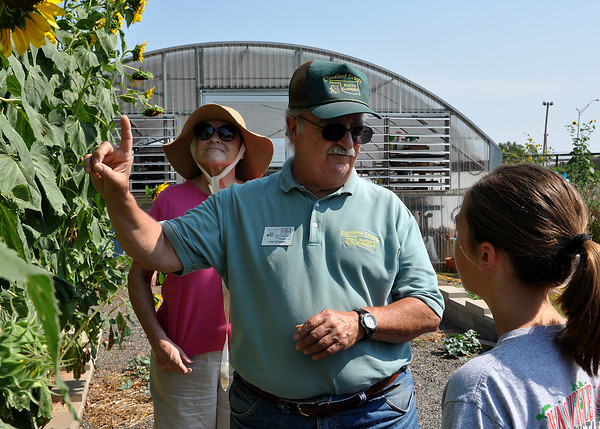 Master Gardeners Barbara Tunney and Fred Schneider explain the significance of the sunflower to Courtney Gates in the Native American Garden in the Master Gardeners Garden at the Cleveland County Fairgrounds on Wednesday. The Master Gardener's give free tours on Wednesdays and Saturdays from 9 to noon. Julie Bragg/ The Transcript