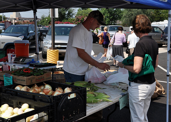 Randy Peters helps a customer during the Farmer Market on Wednesday. Farmer Market is held on Monday and Wednesdays from 9 to noon selling vegetables, plants, spices and other home-grown products. Julie Bragg/ The Transcript