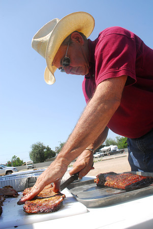 Sam Ott gets his ribs ready to be judged at a a pre-judge event for the Smokin' Up A Storm charity cookoff. The actual event wil be held next weekend at the Cleveland County Fairgrounds with all proceeds going to benifit Food for Friends and the Today Food Bank. Kyle Phillips/The Transcript