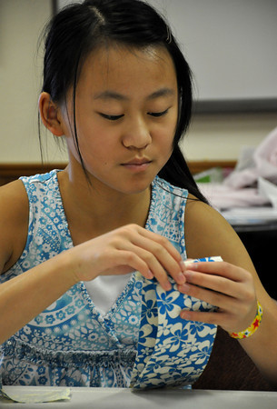 Karina Feng puts together her duct tape wallet on Friday. 4-H members can enter duct tape crafts in the Cleveland County Fair in September and the State Fair in the duck tape category in September. Julie Bragg/ The Transcript