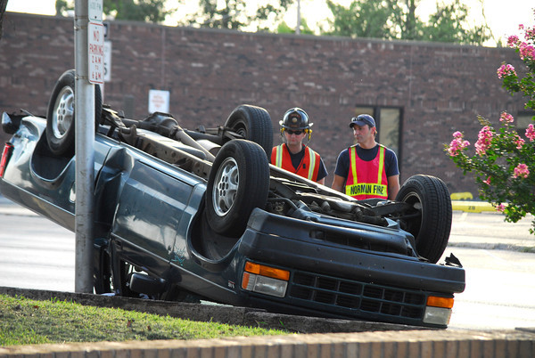 Norman firefighters asses the damage of a two-vehicle accident on Peters Ave. and Grey Street Saturday evening that left one car upside down.  No one was injured in the accident.<br /> Kyle Phillips/The Transcript