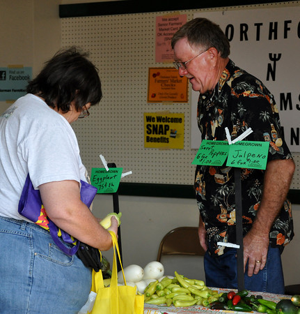 Farmer Mark Gough helps a customer with selecting vegetables from his booth at the Farmers Market on Saturday. Julie Bragg/ The Transcript