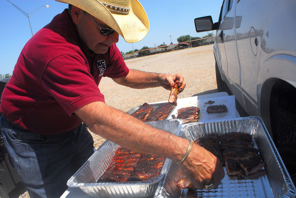 Sam Ott lines up his ribs as he prepares them to be judged at a a pre-judge event for the Smokin' Up A Storm charity cookoff. The actual event wil be held next weekend at the Cleveland County Fairgrounds with all proceeds going to benifit Food for Friends and the Today Food Bank. Kyle Phillips/The Transcript