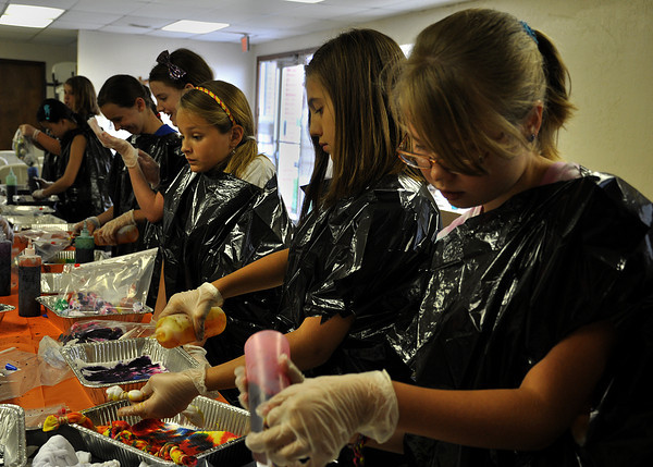 4-her's put their personal touches on tie-dye shirts during the 4-H Tie-Dye workshop on Monday. 4-Her's across Cleveland County attend workshops during the summer to make projects for the Cleveland County fair in September. Julie Bragg/ The Transcript