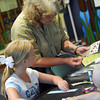 Park Naturalist Kathy Furneaux helps Alyssa Rogers make a bird-themed bookmark Saturday during Bird Day at Discovery Cove Nature Center at Lake Thunderbird.<br /> Kyle Phillips/The Transcript.