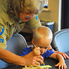 Park Naturalist Kathy Furneaux, left, helps Mason Rogers, 8, draw a design on his bookmark Saturday afternoon during Bird Day at Discovery Cove Nature Center at Lake Thunderbird.<br /> Kyle Phillips/The Transcript