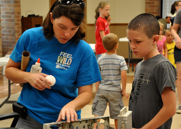 "Linda Jones and son, Coleman Jones, 11, collect supplies to build a droid during Star Wars week at the Noble Public Library on Wednesday. Kids construct a ""droid"" with materials provided for them, and enter a contest for the best droid. Julie Bragg/ The Transcript"
