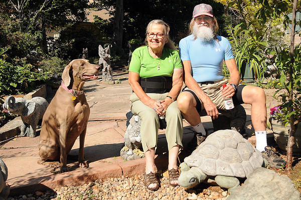 Jeanie and Eddie Smith take a break with their live and concrete managerie of animals in their front yard. Jerry Laizure / The Transcript