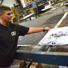 Kathy Walker looks at the first Western Conference Championship t-shirts to roll off the line at Hard Edge Design screen print machine late Thursday night.  The company will screeen print 10,000 shirts for Adidas, with whom they have a sports appearal contract, and delivered them to retailers around the Metro by noon today.  To see a video of the process of printing the shirts visit normantranscript.com