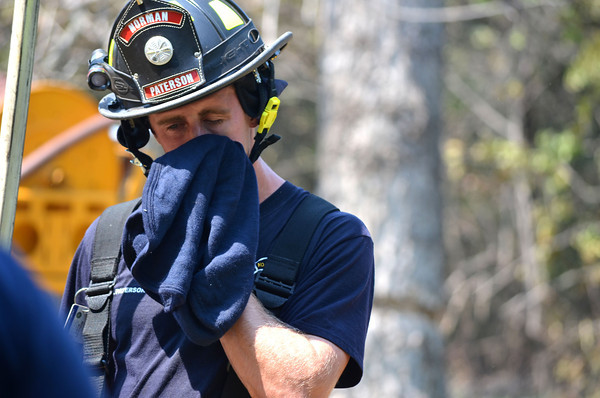 Norman firefighter Justin Patterson wipes sweat out of his face as he tries to cool off after putting out a fire on North Timberline Dr. Wednesday afternoon.<br /> Kyle Phillips/The Transcript