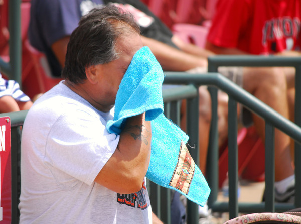 Jeff Blalock wipes the sweat from his face Saturday afternoon as he watches his daughter play in the All-State Slowpitch softball game at the OU Softball Complex.  Temperature in Norman rose above 90 degrees Saturday leaving many residents trying to find ways to keep cool.<br /> Kyle Phillips/The Transcript