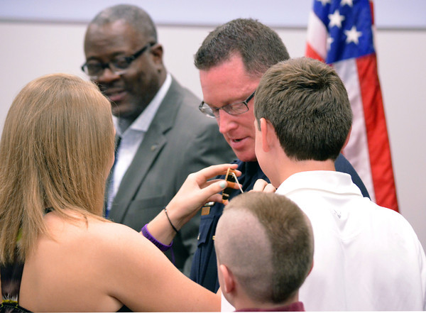 Lieutenent Jeffrey Robertson's children pin his new badge on him as his promotion ceremony Friday afternoon at the Municiple Courtroom. Norman Chief of Police, Keith Humphrey selected Robertson to be promoted from sergeant to the rank of lieutenant.<br /> Kyle Phillips/The Transcript