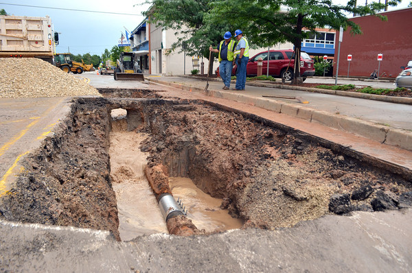 Workers from the City of Norman's Wastewater Management crew prepare to refill a hole in Peters Ave. just south of Main Street Thursday afternoon after they repaired a break in a water main under the road. Kyle Phillips/The Transcript