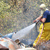 Norman Firefighter matt Seagrest sprays out hot spots after two sheds burned to the ground in a fire on North Timberline Dr. Wednesday afternoon.  No one was hurt in the blaze, and the cause is still inder investigation.<br /> Kyle Phillips/The transcript