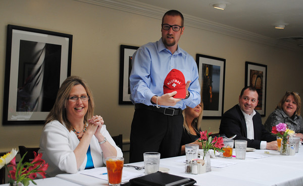 """Incoming Norman Convention and Visitors Bureau Board of Directors chair, Kris Glenn accepts a hat reflecting his desire to stay """"neutral, like Switzerland."""" The comment came in earlier debates over positions the NCVB Board took on city policy. Transcript Photo by Joy Hampton"""