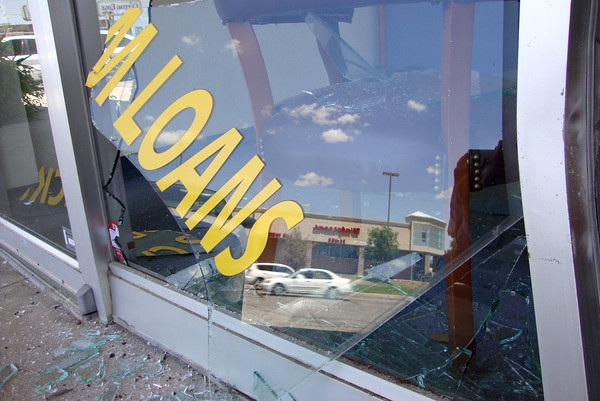 Shards of plate glass from the storefront of Checkmate, 614 W. Main St., rest on the sidewalk and inside the term loan business. Manager Sabra Smith said the driver of a gold-colored, four-door vehicle drove away after smashing into the storefront at about 1:30 p.m. on Wednesday. The business closed after the collision, and Smith said she was unsure of when regular business would resume. Joel Pruett / The Transcript