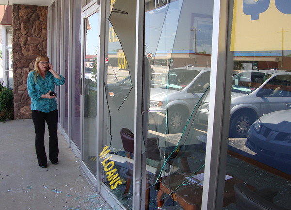 "Checkmate manager Sabra Smith takes business calls from the sidewalk in front of her 614 W. Main St. office. She said the term loan business closed Wednesday at about 1:30 p.m. after a gold-colored, four-door vehicle drove over the curb and into the large, plate-glass windows. The reportedly hit-and-run collision scattered shards of glass throughout the business and caused structural damage to the storefront. ""I might have a few nightmares tonight,"" Smith said, though no one inside the business was injured. Joel Pruett / The Transcript"