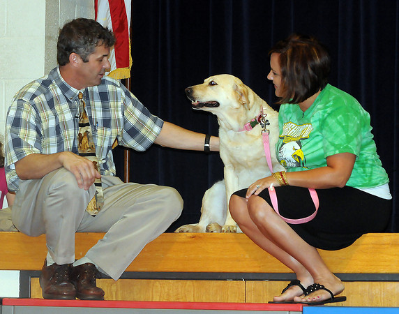 Norman veteranarian Dr. John Otto (left) and Wahington Elementary School teacher Amber Bui sit with therapy dog Sunshine Monday, May 21, 2012, during an assembly at in which Bui, Sunshine's  owner  Bui announced that the dog would be used in Washington classrooms next year. Jerry Laizure/The Transcript