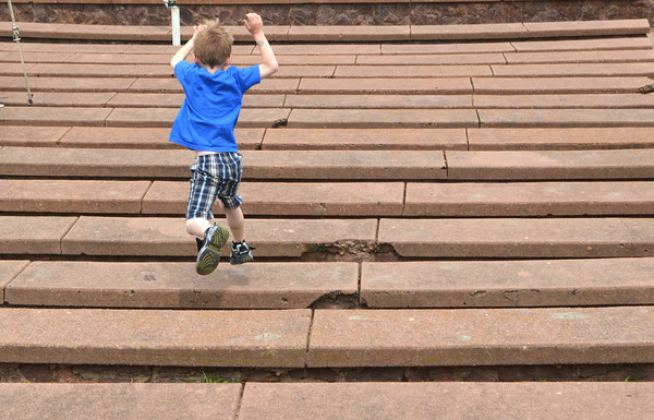 Memphis Cook, 6, jumps down the seats at the ampatheater at Andrews Park Friday afternoon as he and his sister play in the area.<br /> Kyle Phillips/The Transcript