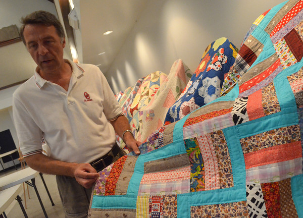Mike Kertok shows off a quilt made by  his mother, who passed in March,  that is on display at First Christian Church Friday afternoon.  Kurtok says after the quilts are taken off display he will disperse them amoungst family members who want them.<br /> Kyle Phillips/The Transcript