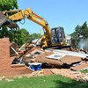 A worker demolishes a building on the property of University Lutheran Church and Student Center Wednesday afternoon to make room for a green area.  The church is hoping to have a fundaraiser in the fall to raise money for the trees and other plants for the area.<br /> Kyle Phillips/The Transcript