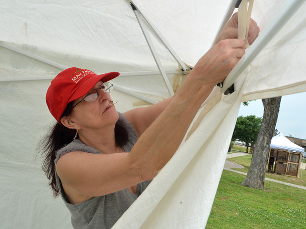 Carolyn Joy Brown pins her tent to its frame as she sets up her booth Friday afternoon in anticipation of the May Fair Arts Festival which will be at Andrews Park all day today.<br /> Kyle Phillips/The Transcript