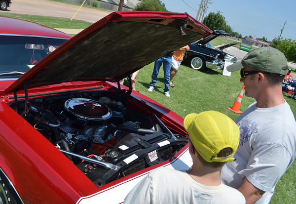 Rob Caruso and his son Garrison look at the engine on a 1968 Chevrolet Camero SS at Norman Community Church of the Nazarene's Car Show that benifits the church's student ministries mission trip.<br /> Kyle Phillips/The Transcript