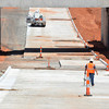 A contruction worker walks down a paved portion of the Robinson Street Underpass project Wednesday afternoon.  According to the City of Norman website, the construction of the Robinson Street Underpass is approximately 70% complete including the completion of the storm water lift station, the permanent railroad bridge and the majority of the excavation of Robinson Street.<br /> Kyle Phillips/The Transcript