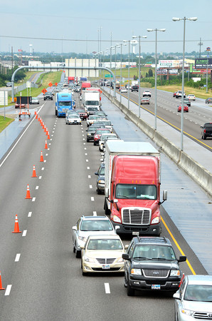 Drivers merge into one lane on Interstate 35 at Tecumseh Rd. to avoid crews cleaning up an accident site where a semitrailer rolled over after hitting two other vehicle around 3:30 a.m. Sunday morning.<br /> Kyle Phillips/The Transcript