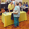 "Larry Slaughter talks with a customer at the Hearing Loss Association of Oklahoma booth at the 37th Annual Oklahoma Conference on Aging ""Secrets of Aging: Hidden Treasures"" Wednesday at the Embassy Suites.<br /> Kyle Phillips/The Transcript"